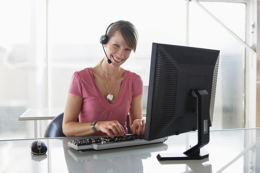 Frau mit Headset am Bildschirm